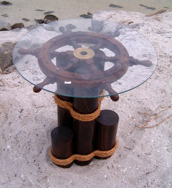 glass top table built on ship wheel